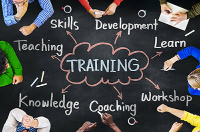 "Image of people around a chalkboard-like table with the word ""TRAINING"" in the center"