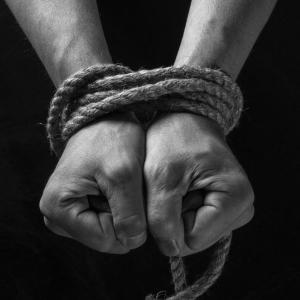 Female hands tied up with rope
