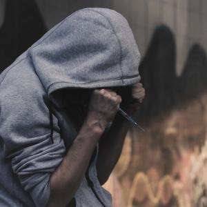 Person in a hoodie with syringe