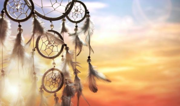 A picture of a sunset in the background with a dream catcher in the foreground.