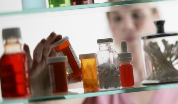 woman looking through medicine cabinet