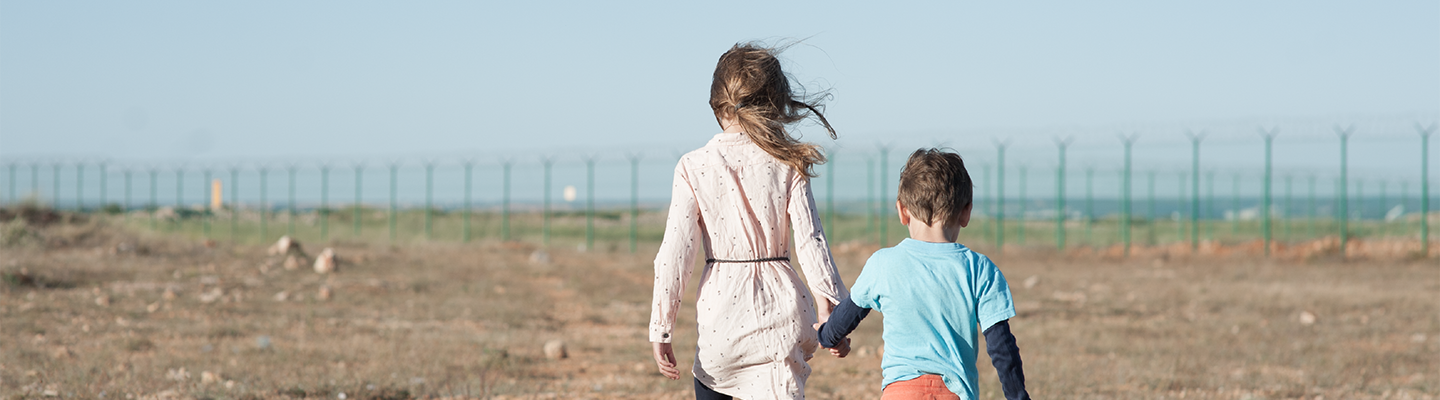 Two children holding hands walking towards fence